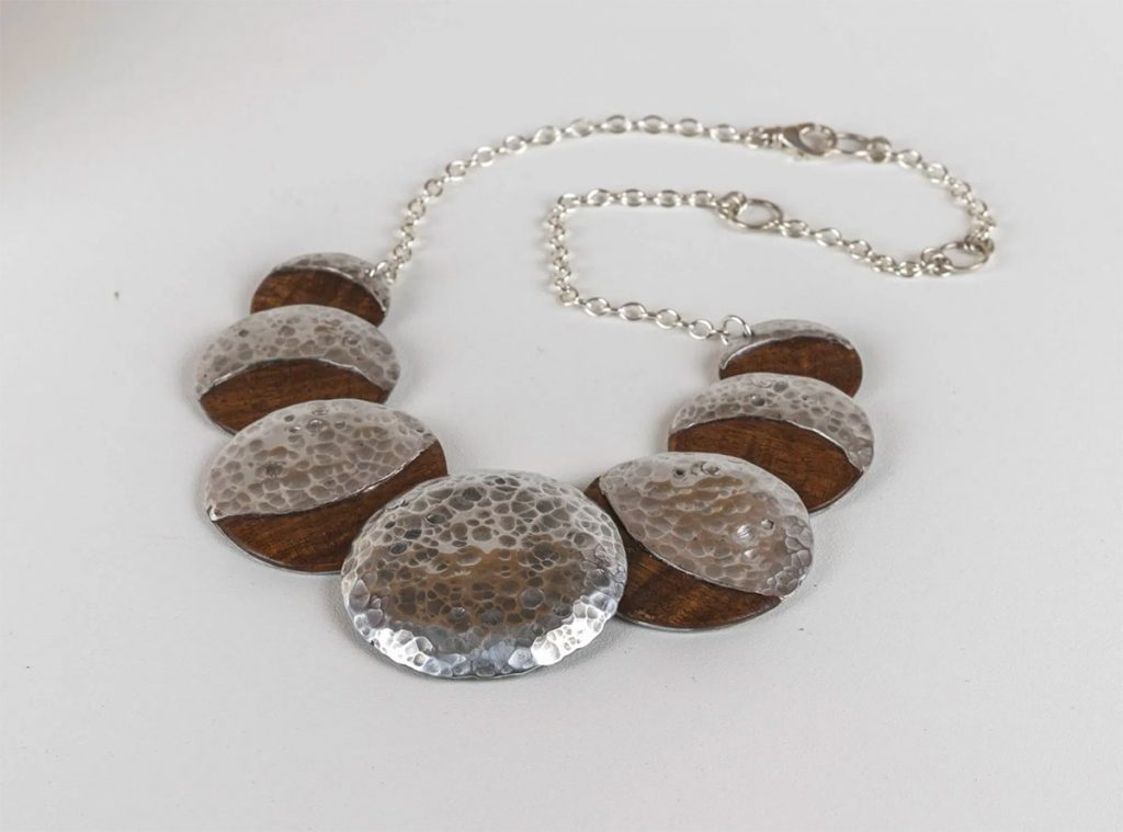 Necklace of 7 wooden medallions embellished with silver.